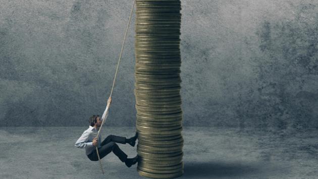 Ein Mann klettert mit einem Seil an riesigen gestapelten Münzen nach oben.