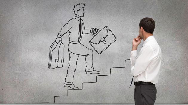 Ein Mann in Hemd schaut auf eine Wandzeichnung eines Mannes, der mit einer Aktentasche eine Treppe hinaufsteigt.