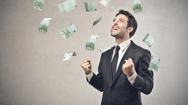Ein Mann in Anzug steht in einem Geldregen aus 100-Euro-Scheinen und lacht.