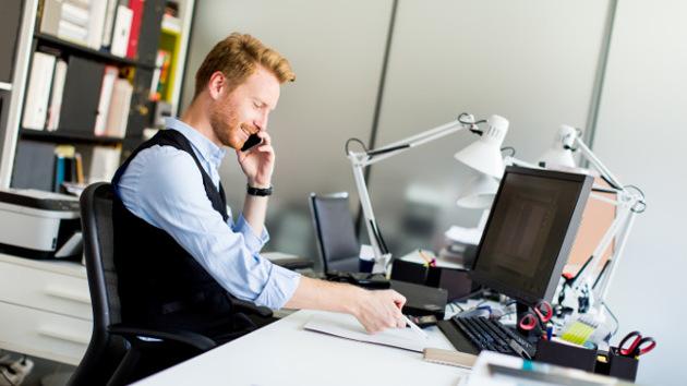 Ein Mann in Hemd sitzt im Büro vor seinem Computer und telefoniert lächelnd.