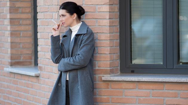 Eine Raucherin in grauem Mantel steht mit einer Zigarette in der Hand vor einem Gebäude.