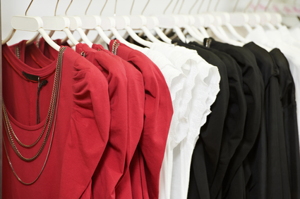 Mehrere Kleider hängen auf einer Kleiderstange in einem Bekleidungsgeschäft.
