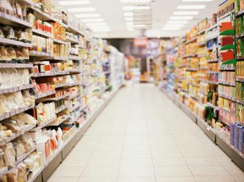 Langer leerer Gang zwischen vollen Regalen in einem Supermarkt