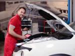 Ein Kfz-Mechatroniker nimmt Messungen im Motorraum eines Autos vor.