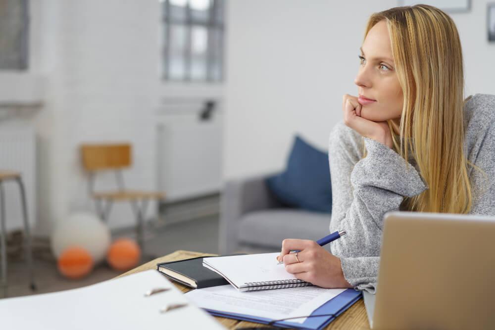 Eine junge Freiberuflerin sitzt nachdenkend an ihrem heimischen Schreibtisch.