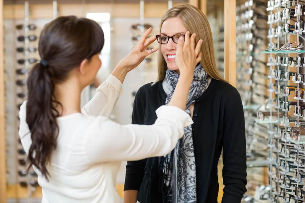Eine junge Augenoptikerin berät eine Kundin bei der Auswahl ihrer Brille.