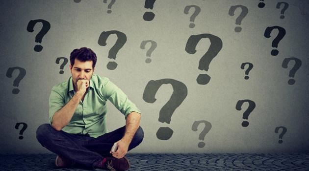 Ein Arbeitssuchender sitzt grübelnd auf seinen Arm gestützt auf dem Boden vor einer Wand mit großen Fragezeichen.