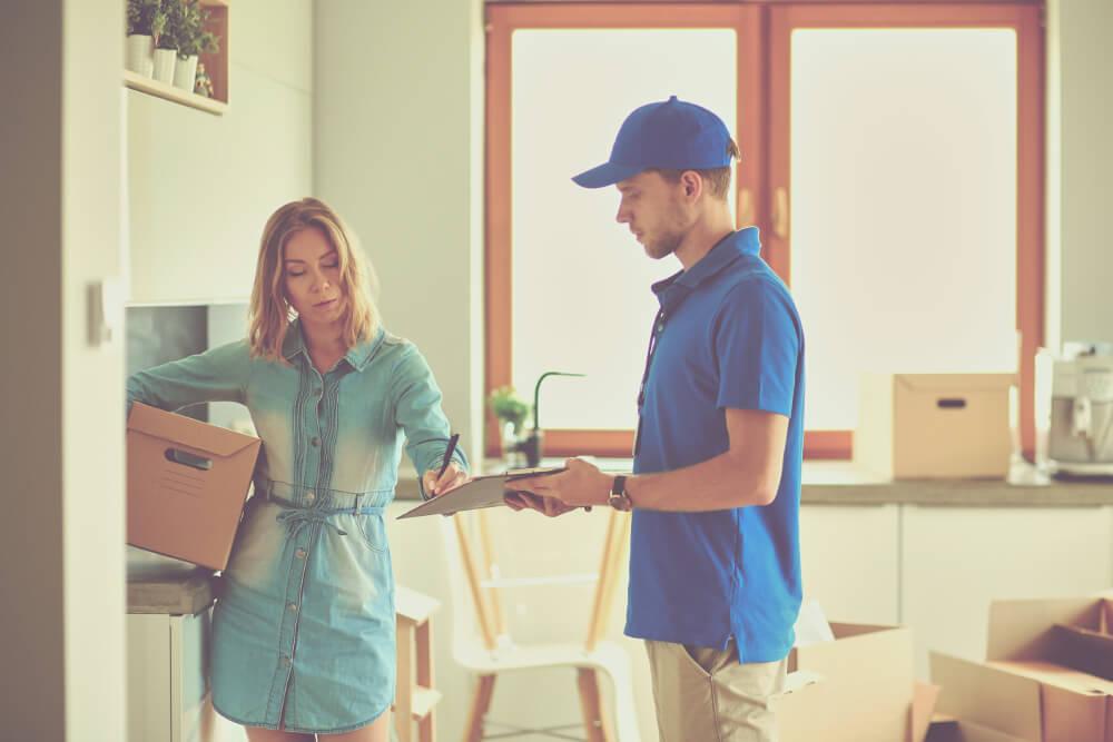 Ein Lieferbote bringt einer Kundin die Ware bis in die Wohnräume.