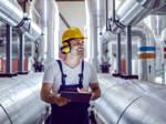 Ein Techniker geht in einem Kraftwerk durch die Reihen der zahlreichen dicken Rohre.