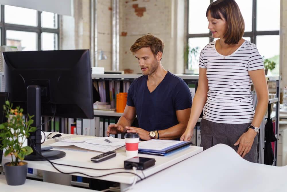 Mann und Frau tauschen sich am Schreibtisch aus