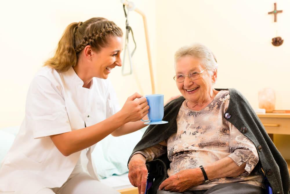 Eine Mitarbeiterin in der Altenpflege kümmert sich um eine ältere Dame.