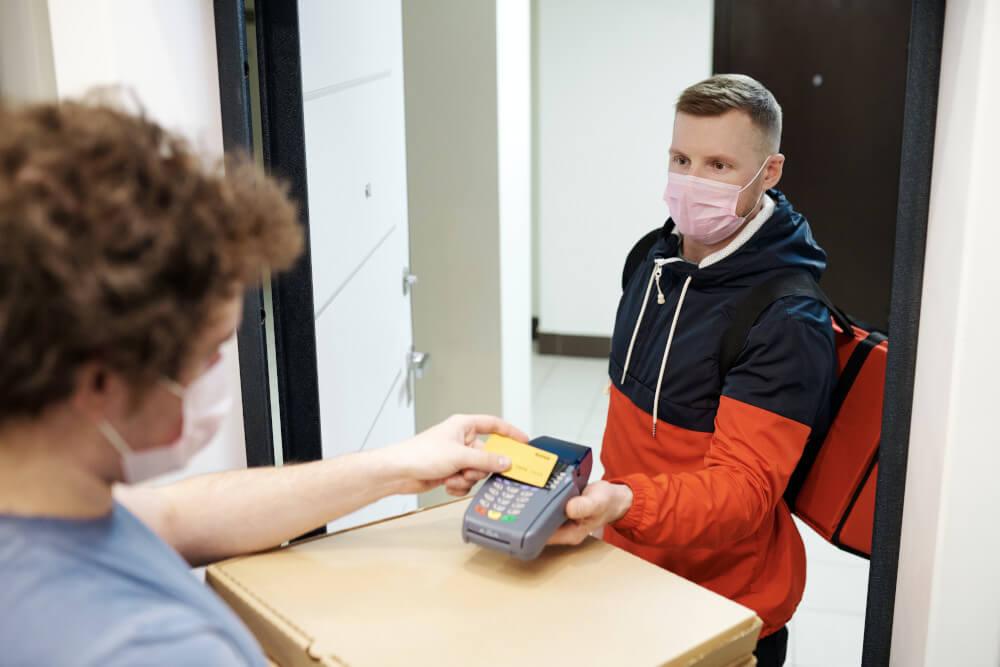 Ein Kunde bezahlt mit der Karte einen Pizzalieferanten an der Tür.