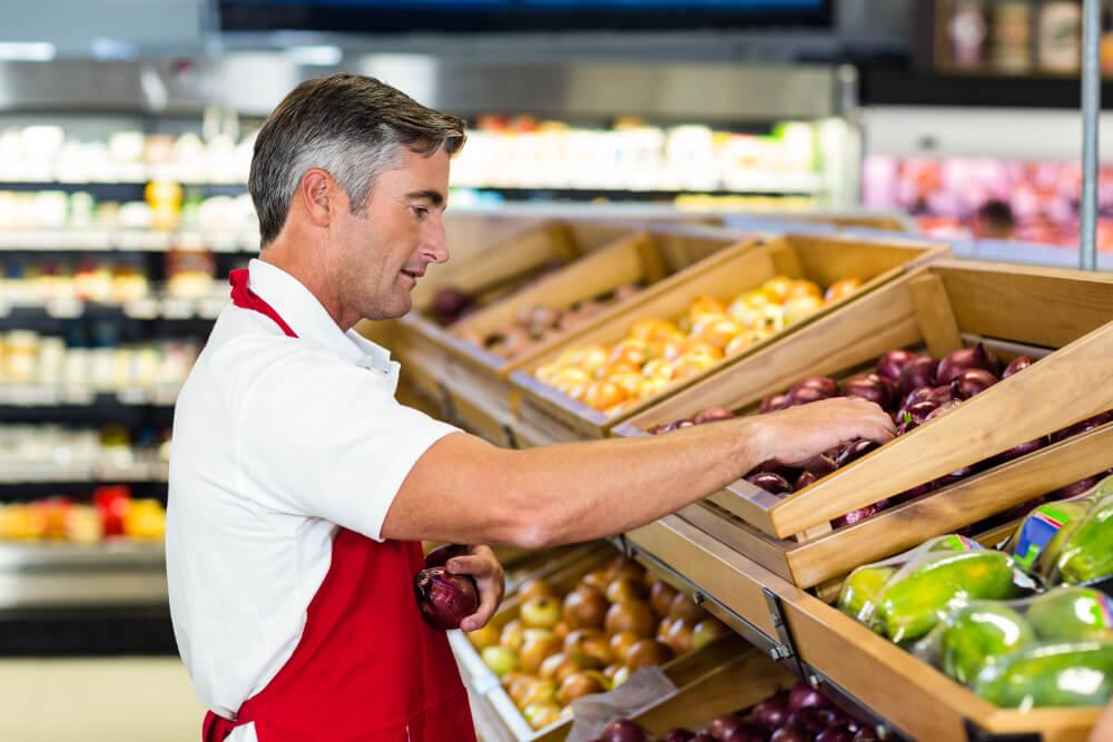 Ein Penny-Verkäufer drapiert frisches Obst auf der Verkaufsfläche im Laden.