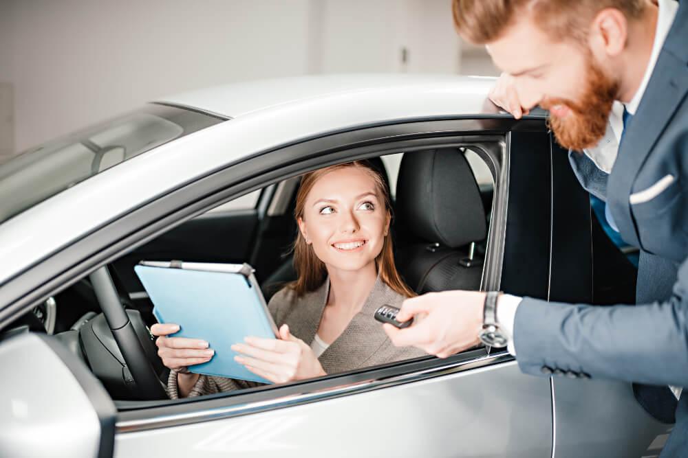Ein Mitarbeiter einer Autovermietung überreicht einer Kundin den Schlüssel für den Mietwagen und wichtige Unterlagen.