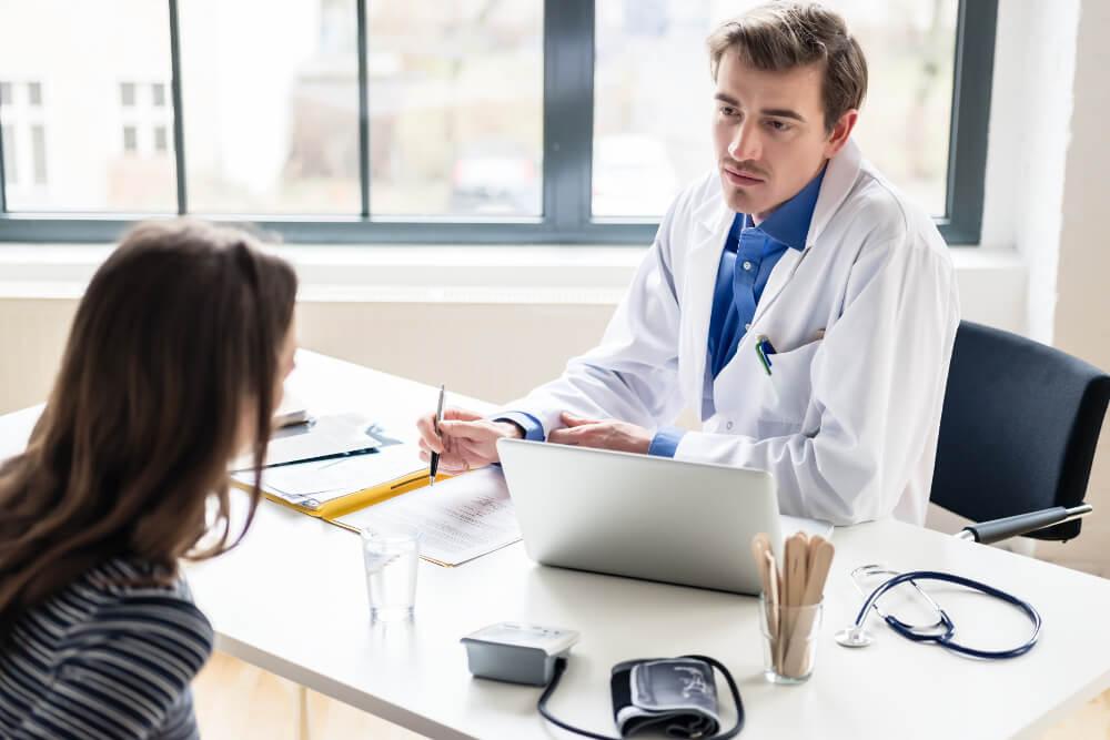 Ein junger Arzt hört einfühlsam und aufmerksam einer jungen Patientin zu.