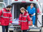 Zwei junge Rettungssanitäter heben eine Krankenliege aus einem Krankenwagen heraus.