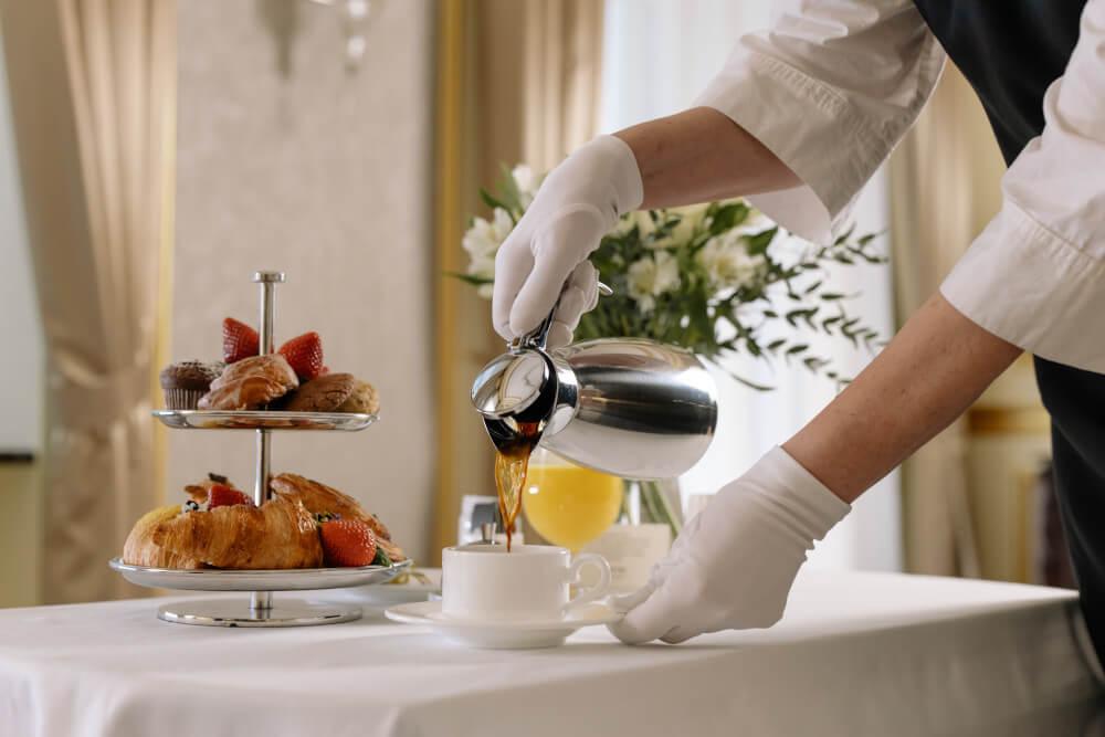 Servicekraft bereitet Frühstück vor.