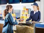 Frau kauft Popcorn bei einer Servicekraft am Kino-Konzessionsstand