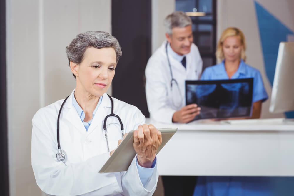 Eine Ärztin, ein Arzt und eine Pflegerin im Krankenhaus analysieren ein Röntgenbild und beratschlagen sich.