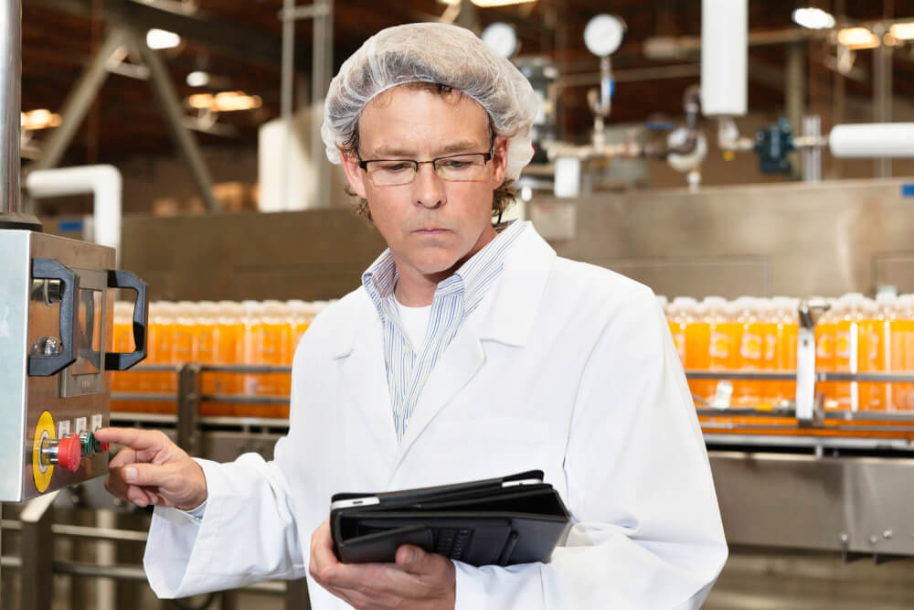 Ein Mitarbeiter in der Lebensmittelindustrie führt an einer Produktionsanlage Kontrollen durch.