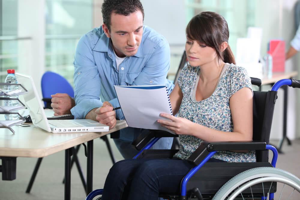 Eine schwerbehinderte Arbeitnehmerin im Rollstuhl bespricht sich mit einem Arbeitskollegen.