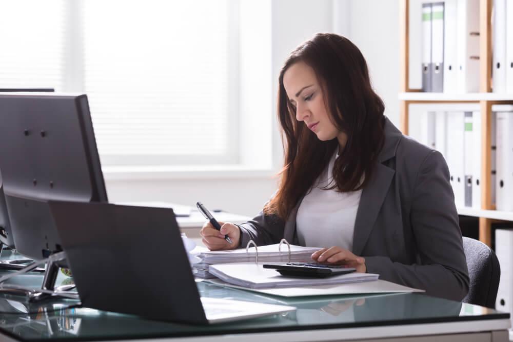 Eine junge Wirtschaftsprüferin prüft Unterlagen in ihrem Büro.