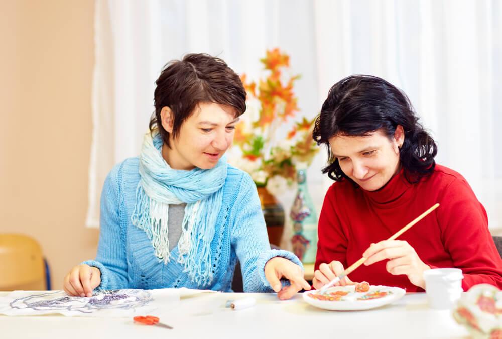 Zwei junge Frauen mit Behinderung arbeiten kreativ.