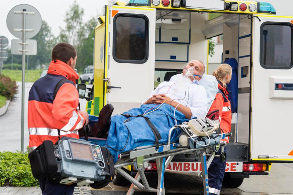 Eine Rettungssanitäterin und ein Notfallsanitäter transportieren einen Patienten auf einer Liege zum Krankenwagen.