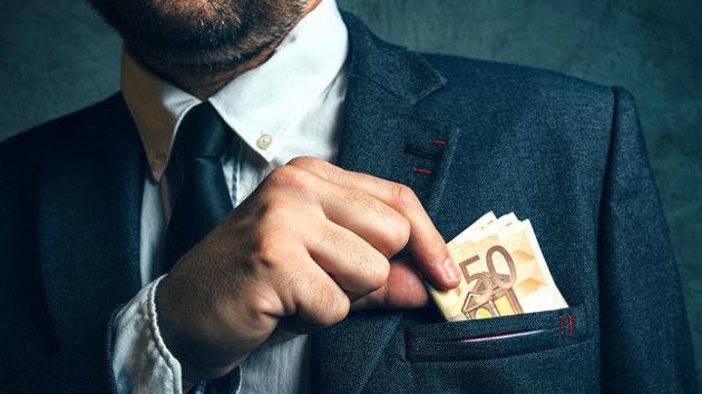 Ein Mann zieht mehrere 50-Euro-Scheine aus seiner Anzugtasche.
