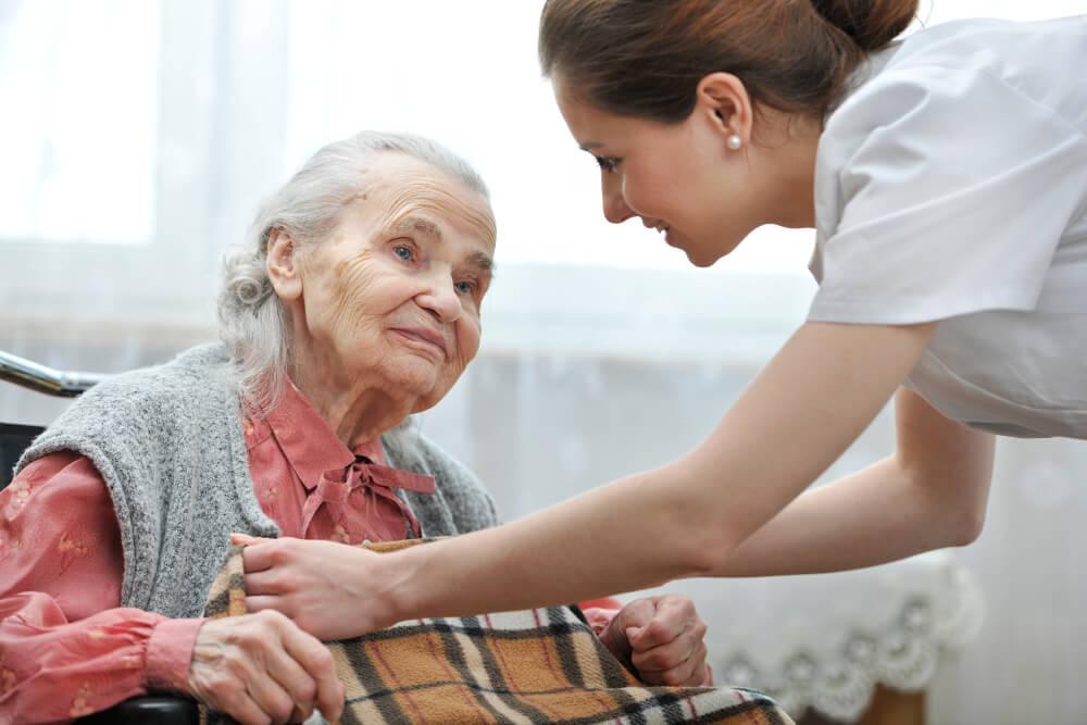 Eine junge Altenpflegerin kümmert sich liebevoll um eine alte Dame.