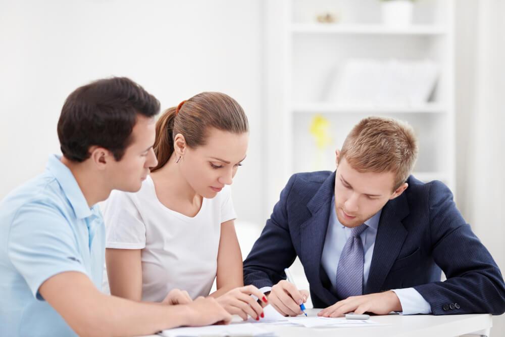 Ein Versicherungsmitarbeiter berät ein junges Paar zu Versicherungsprodukten.