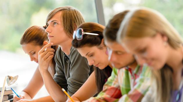 Fünf junge Menschen sitzen in einer Reihe mit Stiften in der Hand.