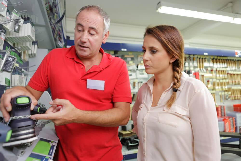 Ein Bauhaus-Mitarbeiter erklärt einer Kundin ein elektronisches Heimwerker-Gerät