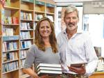 Eine Buchhändlerin und ein Buchhändler mit Büchern und Tablet in ihrem Laden.