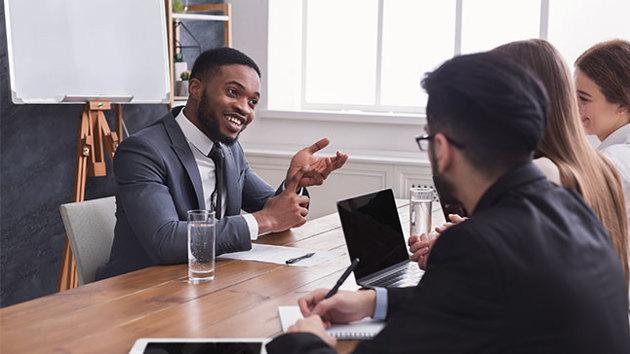 Eine Person im Anzug sitzt drei Personen an einem Tisch gegenüber und führt ein Bewerbungsgespräch