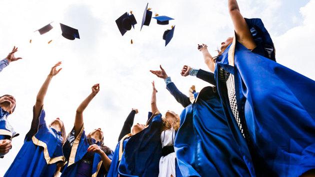Studienabsolventen werfen ihre Doktorhüte in die Luft.