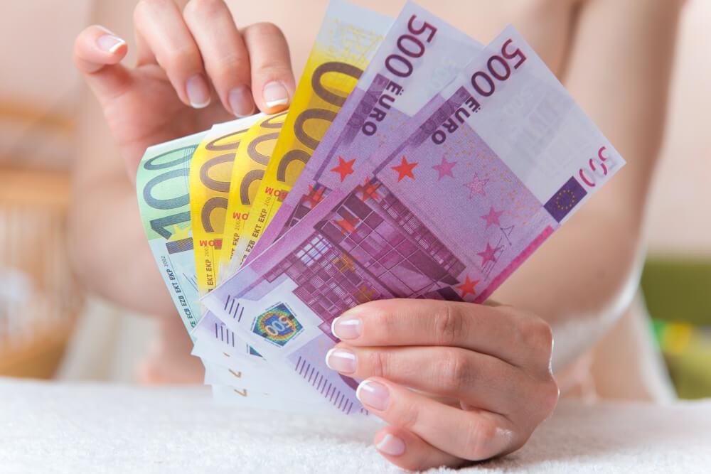 Eine Frauenhand hält gefächerte Geldscheine und zählt diese.