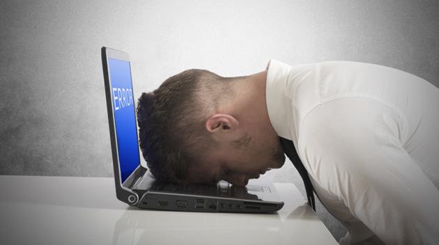 Ein Mann in Hemd liegt mit dem Kopf auf der Tastatur eines Laptops, auf dessen Bildschirm eine Fehlermeldung angezeigt wird.
