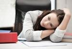 Junge Frau langweilt sich am Arbeitsplatz