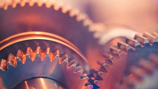 Zahnräder einer Maschine aus Metall werden von rötlichem Licht angestrahlt.