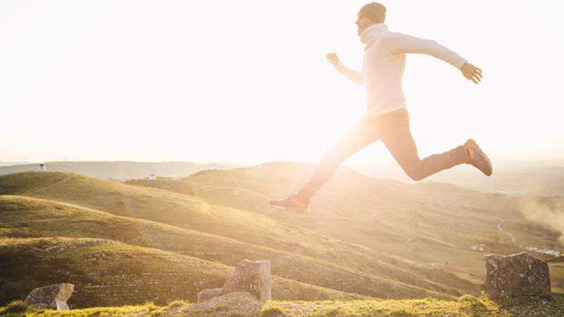 Ein Mann in sportlicher Kleidung springt auf einer grünen Graslandschaft.