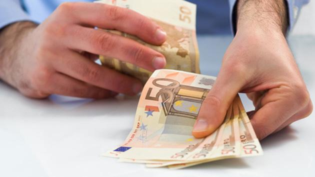 Ein Mann reicht vier 50-Euro-Scheine in Richtung Betrachter und behält weitere Geldscheine in der anderen Hand.