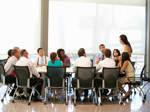 Eine Gruppe von Mitarbeitern einer Firma hat sich um einen großen Konferenztisch versammelt und blickt gebannt auf die Vorgesetzte, die am Kopf des Tisches steht.