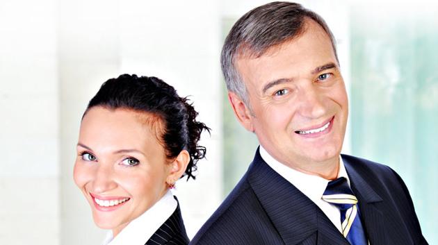 Eine Frau und ein Mann in Geschäftskleidung lächeln.