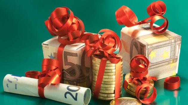 Zahlreiche Geldscheine und Münzen sind zu kleinen Weihnachtsgeschenken gestaltet.