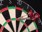 3 Drei Darts-Pfeile stecken in der Triple 20 eines Darts-Boards