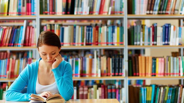 Eine Studentin sitzt in der Bibliothek und liest ein Buch.