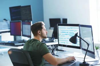 Ein Programmierer sitzt an seinem Arbeitsplatz vor mehreren Bildschirmen und erstellt eine Software.