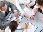 Eine Gruppe Wirtschaftsprüferinnen und Wirtschaftsprüfer tauscht sich zu Zahlen und Ergebnissen aus.