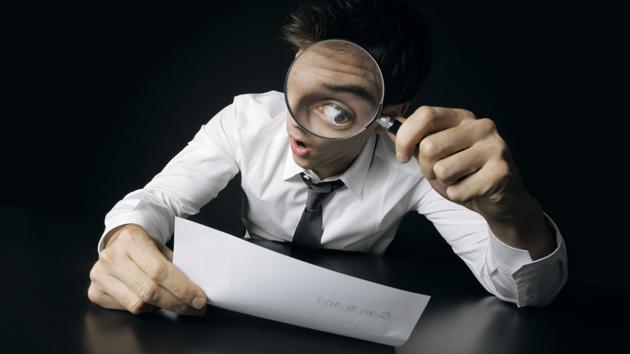 Ein Mann in Hemd und Krawatte schaut durch eine Lupe auf ein Blatt Papier, sodass sein Auge stark vergrößert erscheint.